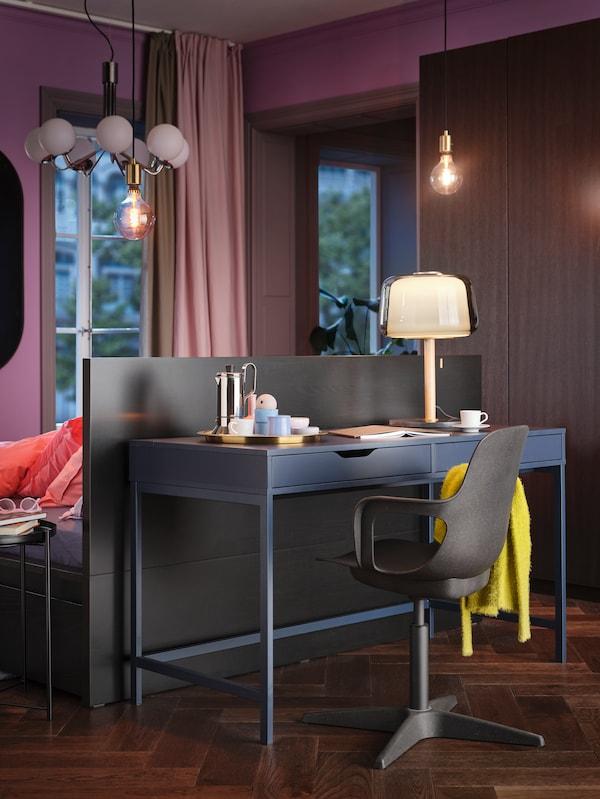 Hálószoba része, ahol egy Alex íróasztal, rajta egy lámpával, és egy forgószék állnak egy MALM ágy fejtámlája mögött.