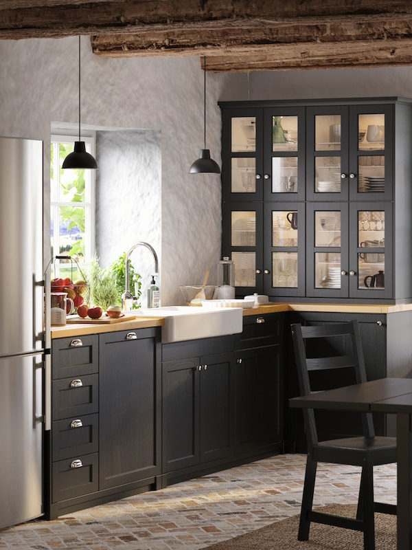 A kitchen with black fronts, chrome handles, and wooden worktop. Two black pendant lamps hang from exposed wooden beams.