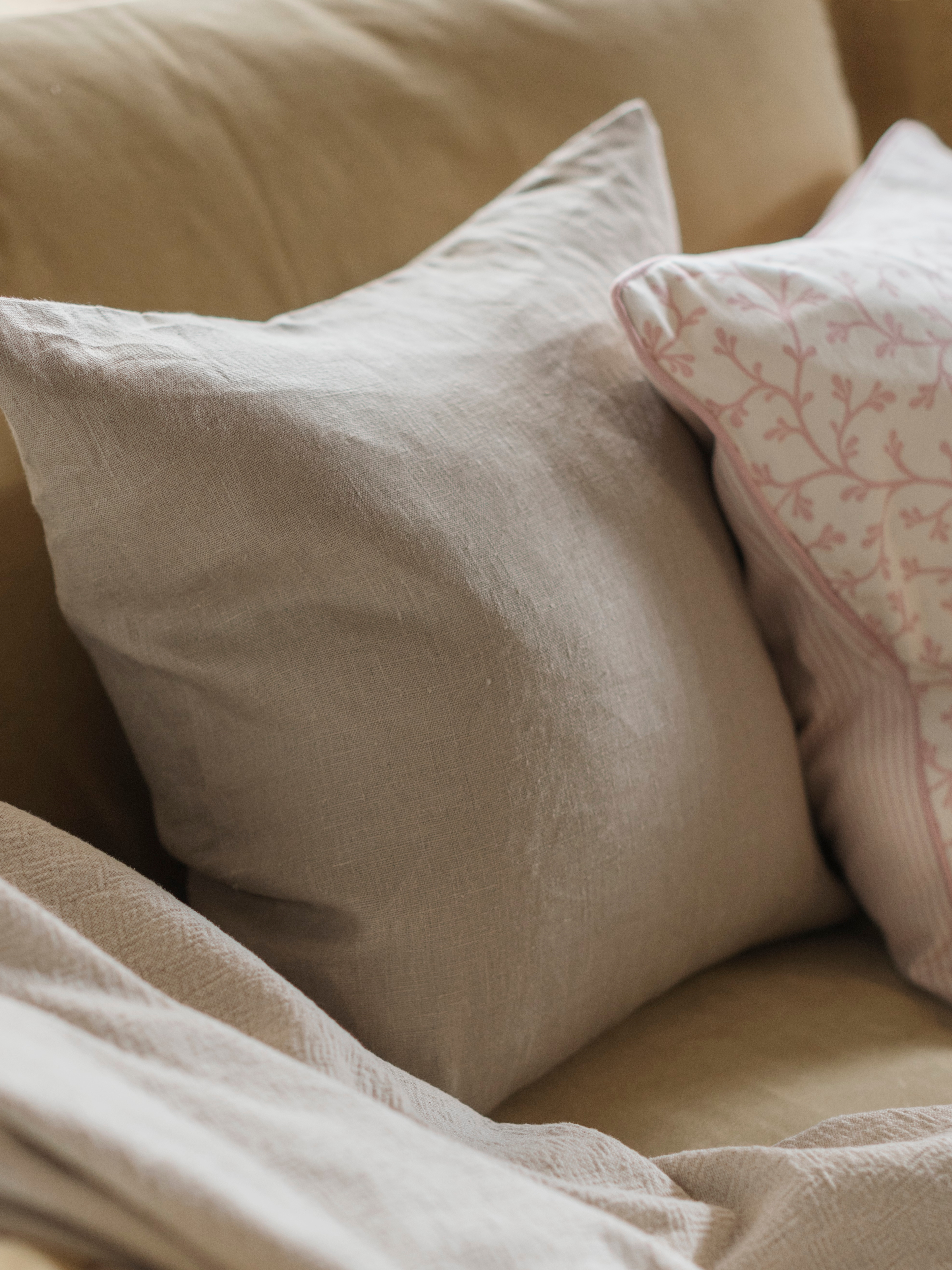 A close-up of a square AINA cushion cover in beige, together with other cushions and a throw on a sofa.