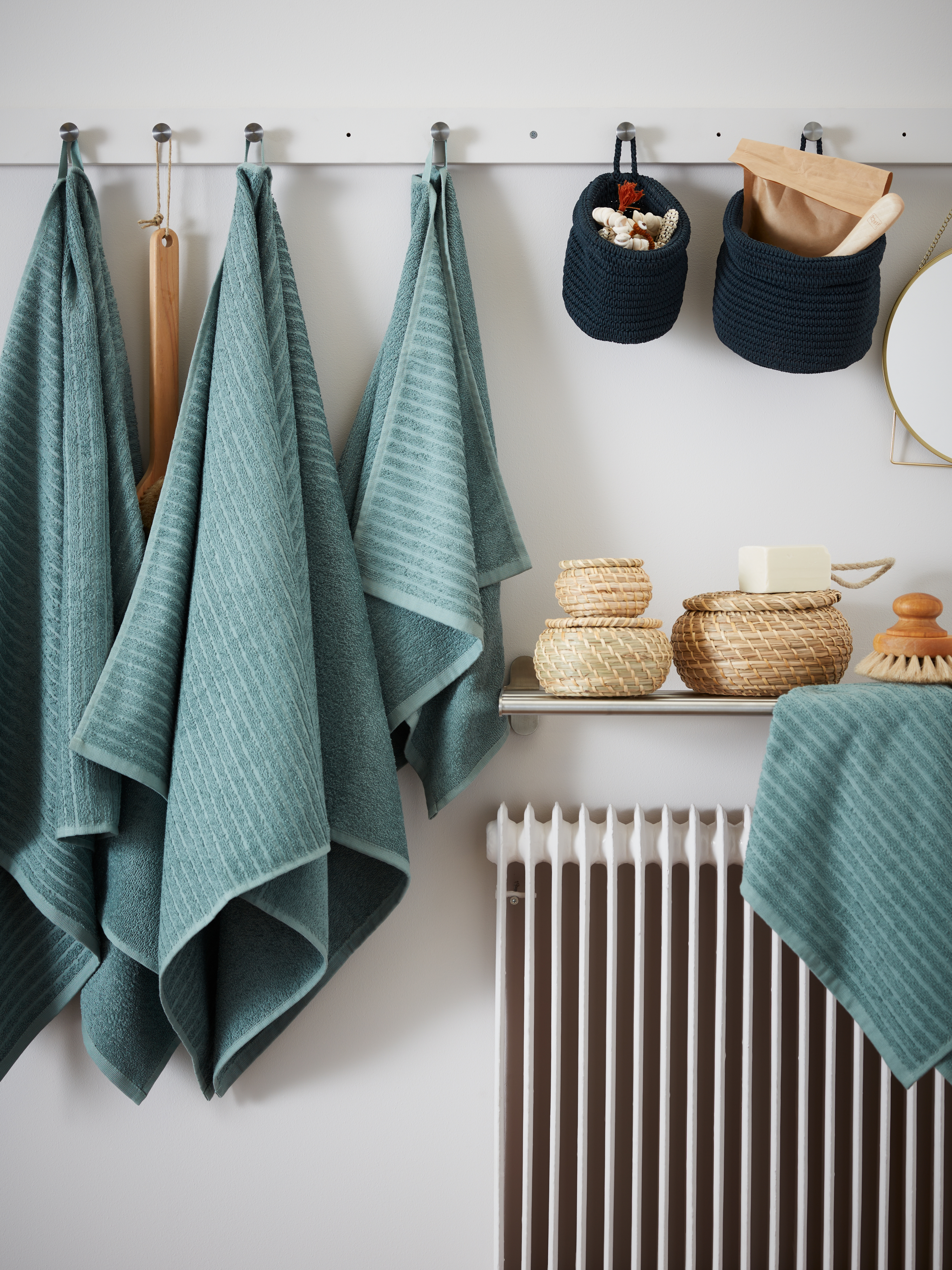 Grey-turquoise VÅGSJÖN towels hanging on a long row of hooks, next to blue NORDRANA baskets with bathroom accessories.