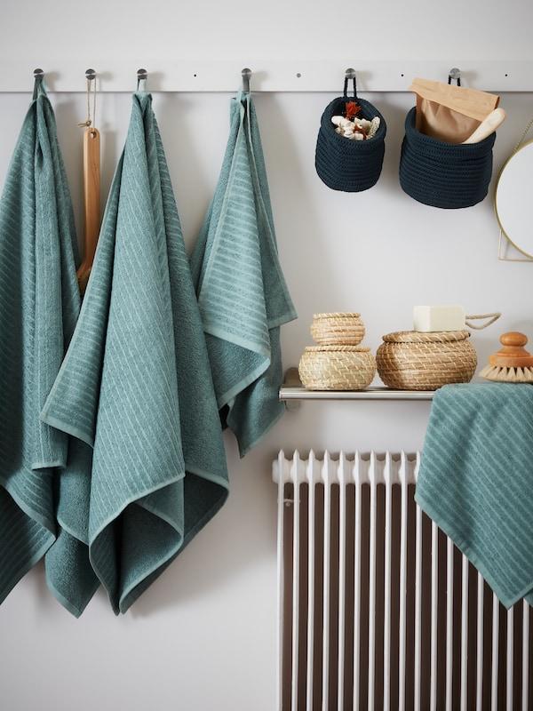 Dos toallas de baño VÅGSJÖN en gris turquesa, una toalla de mano VÅGSJÖN y dos cestas NORDRANA colgadas de ganchos en un riel montado en la pared.