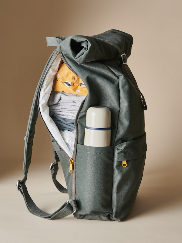 A green DRÖMSÄCK backpack unzipped on one side, filled with clothing, RENSARE bags, and a HÄLSA thermos.