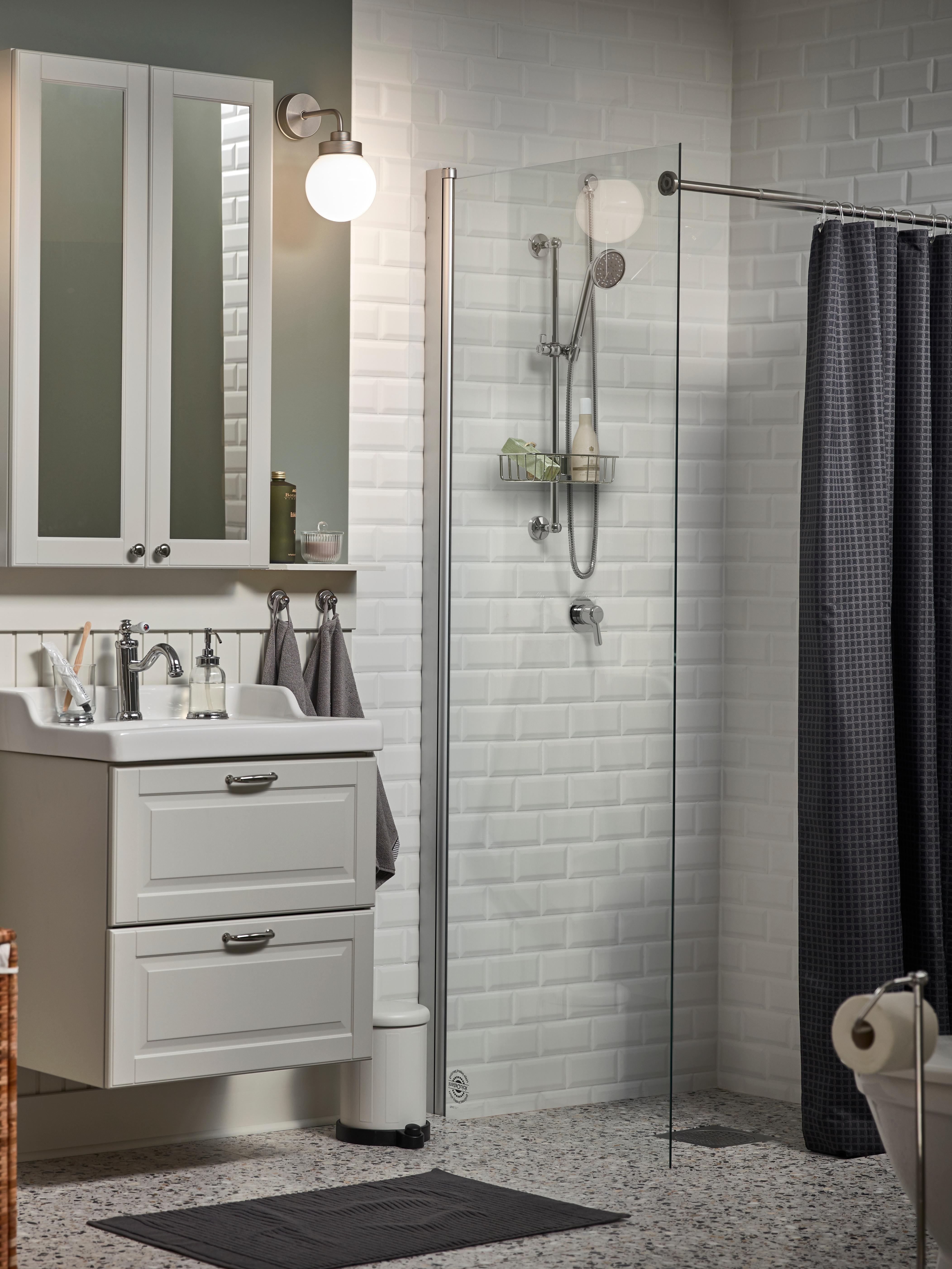 Bathroom with mirror cabinet, wash-stand, bath rug, shower mixer, shower curtain, wall lamp, waste bin, soap dispenser.