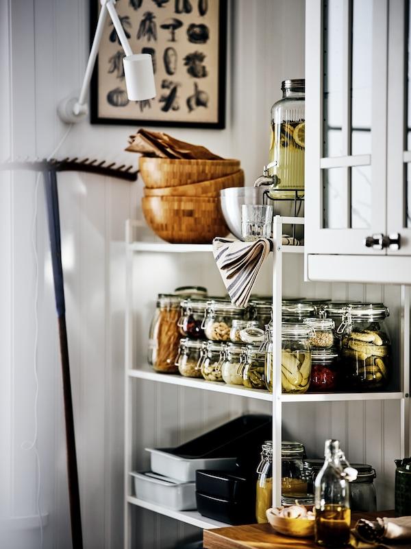 Une étagère JONAXEL blanche dans laquelle sont rangés des bocaux de fruits et légumes, des plats et des saladiers en bois, contre un mur blanc.