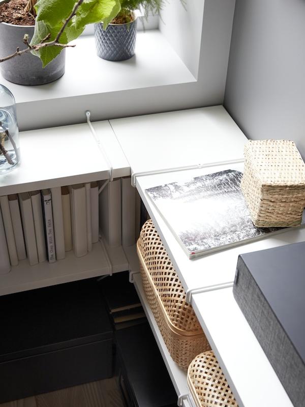 Dva niza belih BERGSHULT/PERSHULT zidnih polica ispod prozora u uglu sobe, između kojih su kutije i knjige.