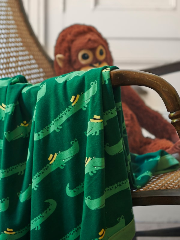 بطانية RÖRANDE منسدلة على ذراع كرسيعليه دمية ناعمة DJUNGELSKOG شكل إنسان الغاب.