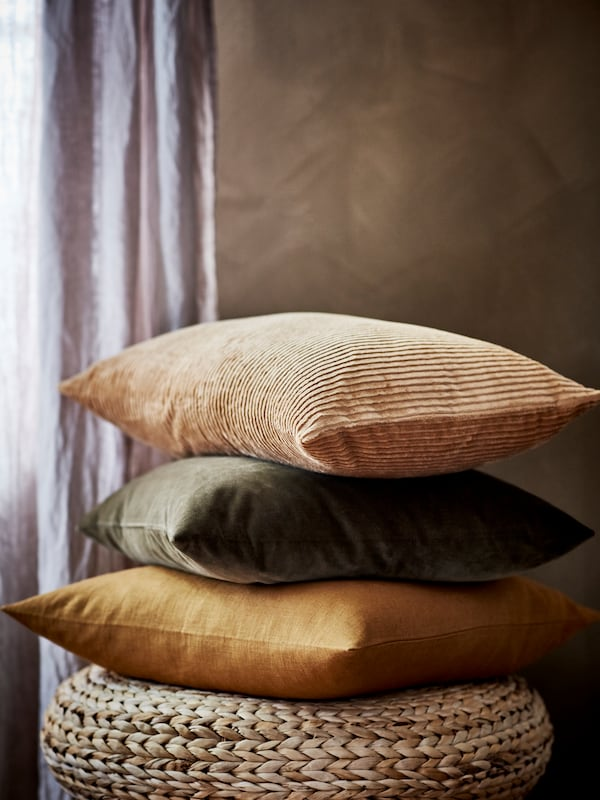 Cushions with a dark golden-brown VIGDIS cushion cover and a dark beige ÅSVEIG cushion cover sit on an ALSEDA stool.