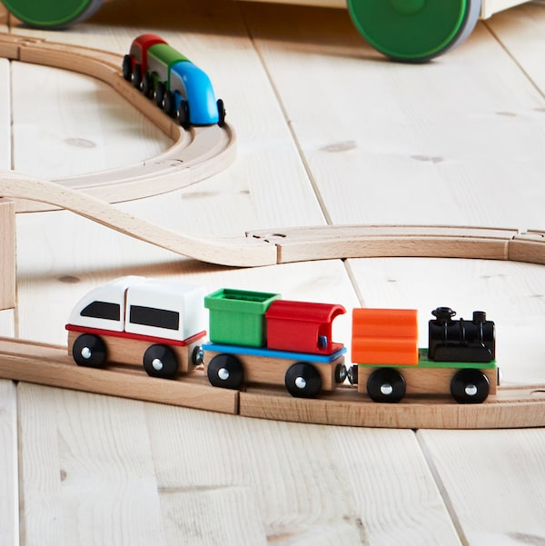 A LILLABO wooden train set is laid out on a wooden floor. Two colourful trains sit on the tracks.