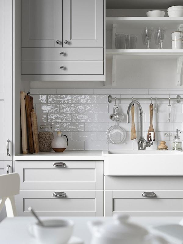 Un pensile grigio chiaro con due ante e cassetti accanto a due mensole bianche a giorno e frontali di cassetti grigio chiaro sotto.