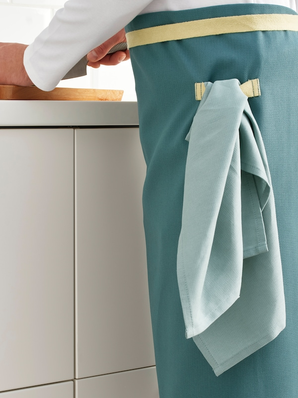 A person stands in a kitchen preparing food and wearing a SANDVIVA waist apron from which a tea towel is hanging.