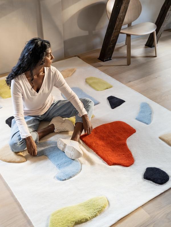 Девушка в джинсах и белой майке сидит на шерстяном ковре ЛОКАЛЬТ ручной работы с объемными красочными вставками.