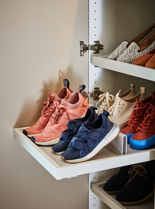 Forskellige sko står på udtrækshylder med en indsats til sko under hælen.