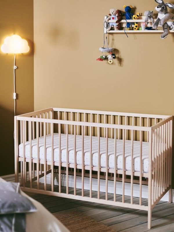 Le coin bébé privilégie le bois naturel: berceau SNIGLAR et rangement mural FLISAT.
