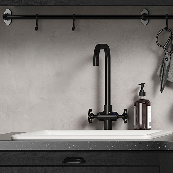 A white kitchen sink and faucet in brushed black metal in front of a concrete-effect wall panel.