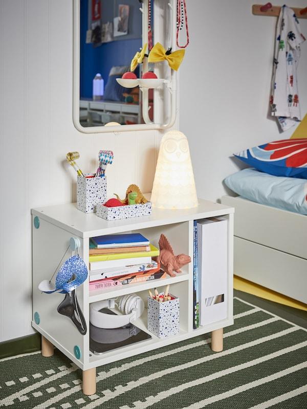 Hvidt sengebord med åbne hylder med bøger, farveblyanter, masker, dinosaurer og en sengelampe, der har form som en ugle.