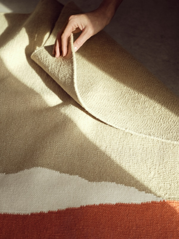 The TVINGSTRUP rug is set on the floor as a hand reaches out to fold a corner of the rug.