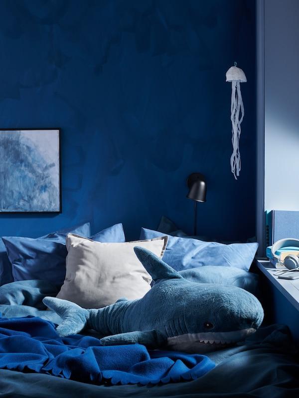 Parte de una habitación en una combinación de colores en azul intenso, con una cama con una manta POLARVIDE en azul oscuro y un peluche BLÅHAJ.