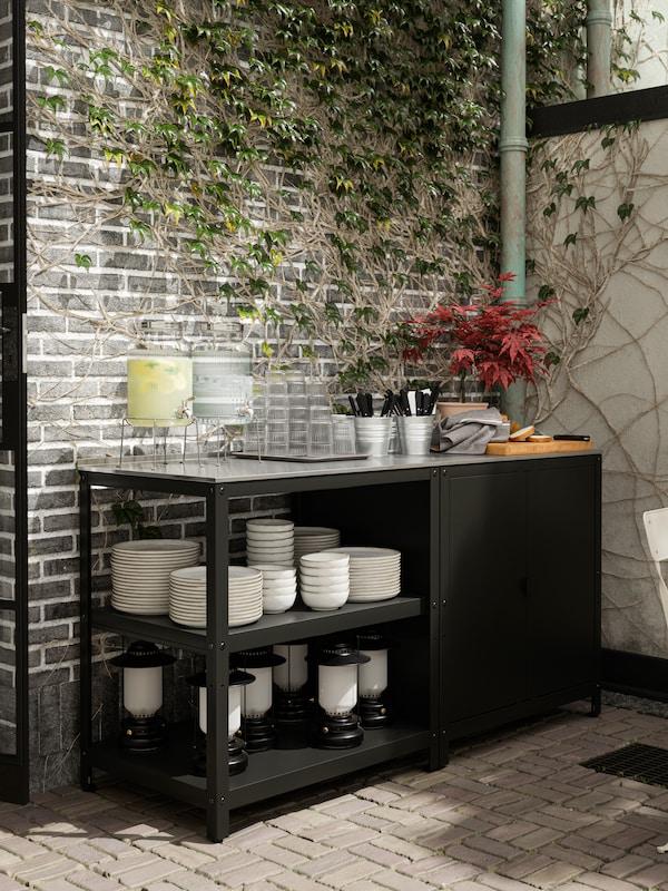 Isola per cucina nera usata come buffet di servizio con acqua, limonata, bicchieri, posate, piatti, ciotole e lanterne.