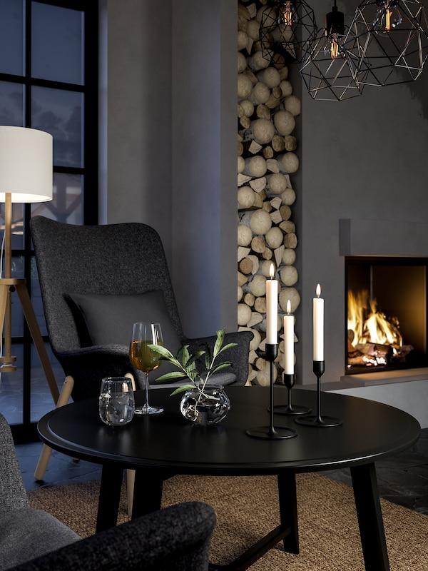 مساحة جلوس بها كرسي بذراعين وظهر مرتفع وطاولة قهوة سوداء وشموع مضاءة ومدفأة.