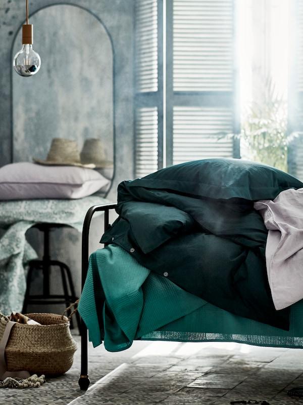 여러 개의 침구가 쌓여 있는 SAGSTUA 삭스투아 침대의 끝부분. 침대 뒤에 발코니 창문이 있는 모습.