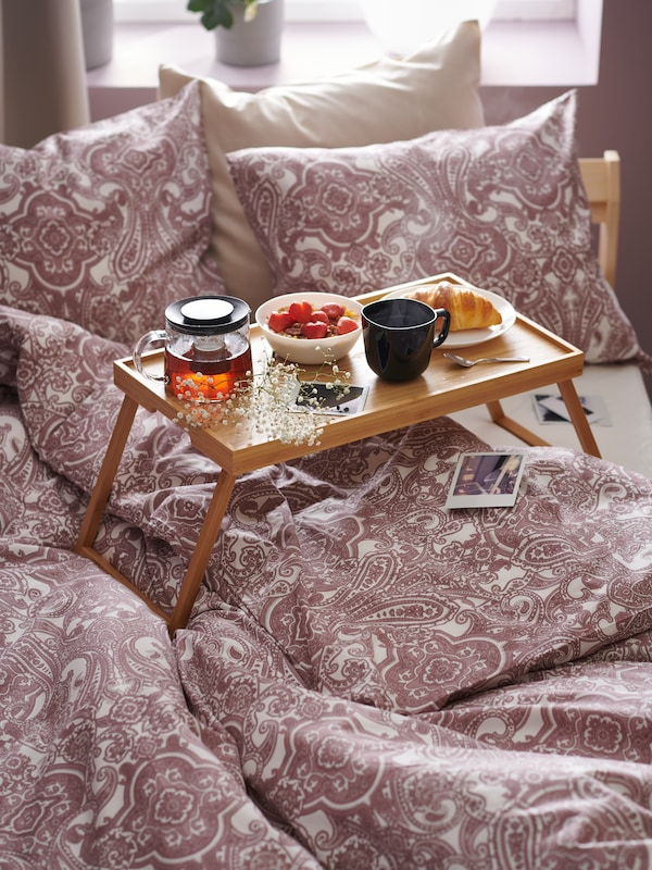 A bamboo breakfast tray placed on an unmade bed with pink duvet covers