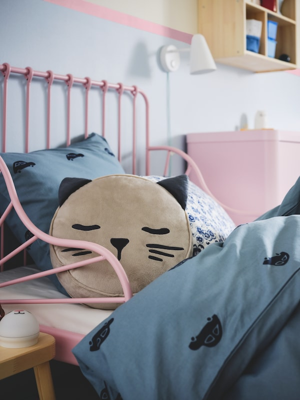 A children's bedroom with a beige BARNDRÖM cushion with pocket and a cat's face and ears in a light pink extendable bed.