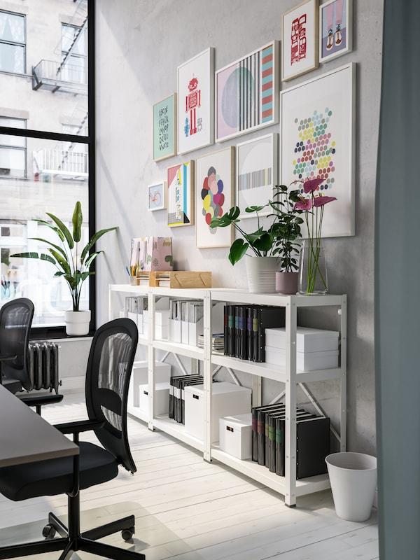 وحدات رفوف بيضاء مع مجلدات سوداء وصناديق بيضاء، وعمل فني ملون في إطار على الحائط ومقاعد عمل سوداء.