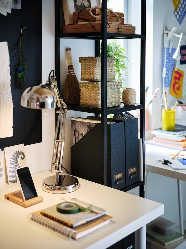 Next to a desk with a white LAGKAPTEN tabletop lit by a FORSÅ work lamp, stands an anthracite ENHET five-shelf high frame.