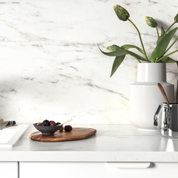 Zaštita od prskanja s imitacijom belog mermera, mali drveni tanjir s trešnjama i bela vaza s lalama.