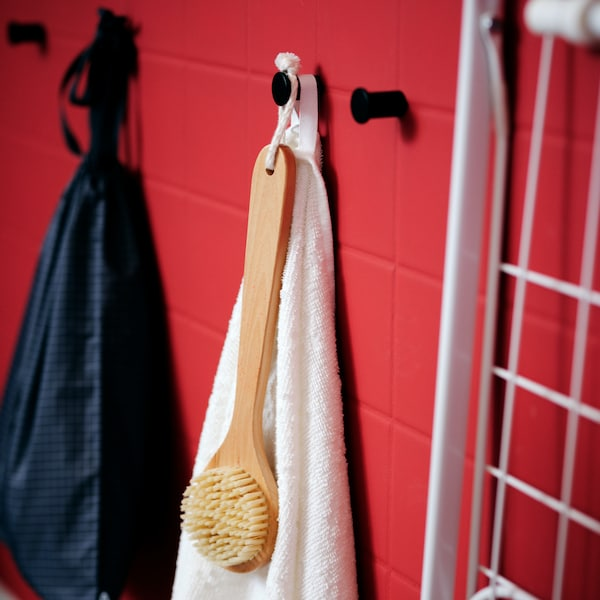 A red-tiled wall with a white VÅGSJÖN bath towel and other bathroom accessories hang from black SKOGSVIKEN hooks.