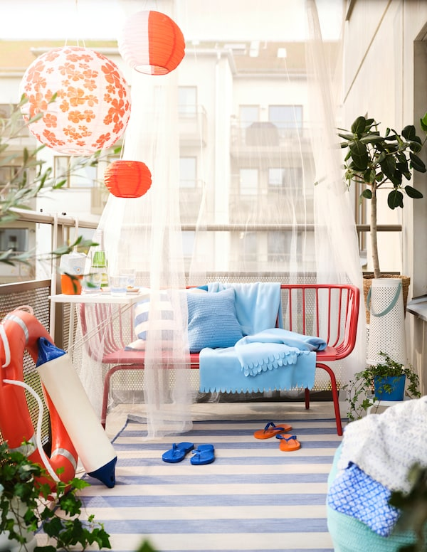 A red outdoor BRUSEN 3-seat sofa with cushions and light blue POLARVIDE throws on it stands on a striped rug on a balcony.