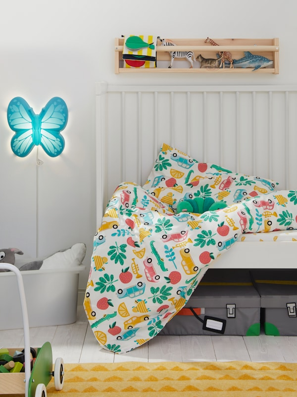 A GULLIVER cot with RÖRANDE bed linen sits under FLISAT wall storage and near a light blue UPPLYST LED wall lamp.