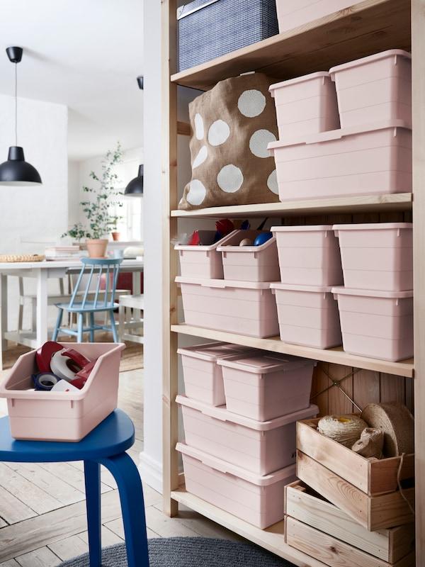 Le scatole rosa SOCKERBIT stanno ordinatamente impilate su uno scaffale aperto.