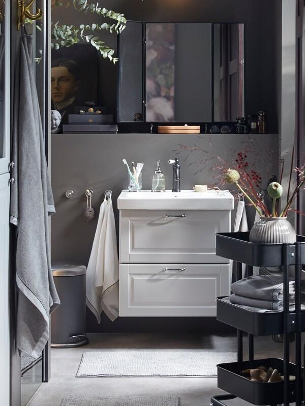 Prikaz GODMORGON svjetlosivog elementa s umivaonikom bijele boje i dvije ladice, crnog stolnog ogledala i bijelih kolica.