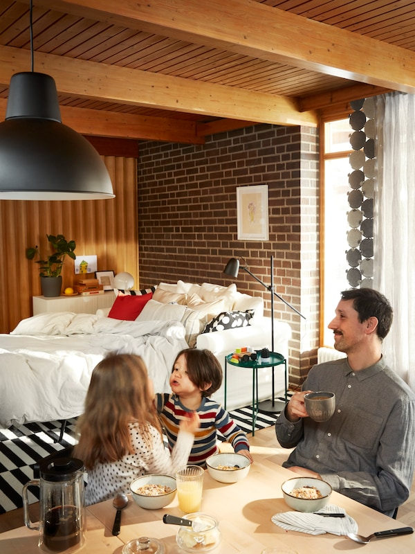 A sofa bed arranged for sleeping, with cover and pillows, and a man with two kids at a breakfast table having breakfast.