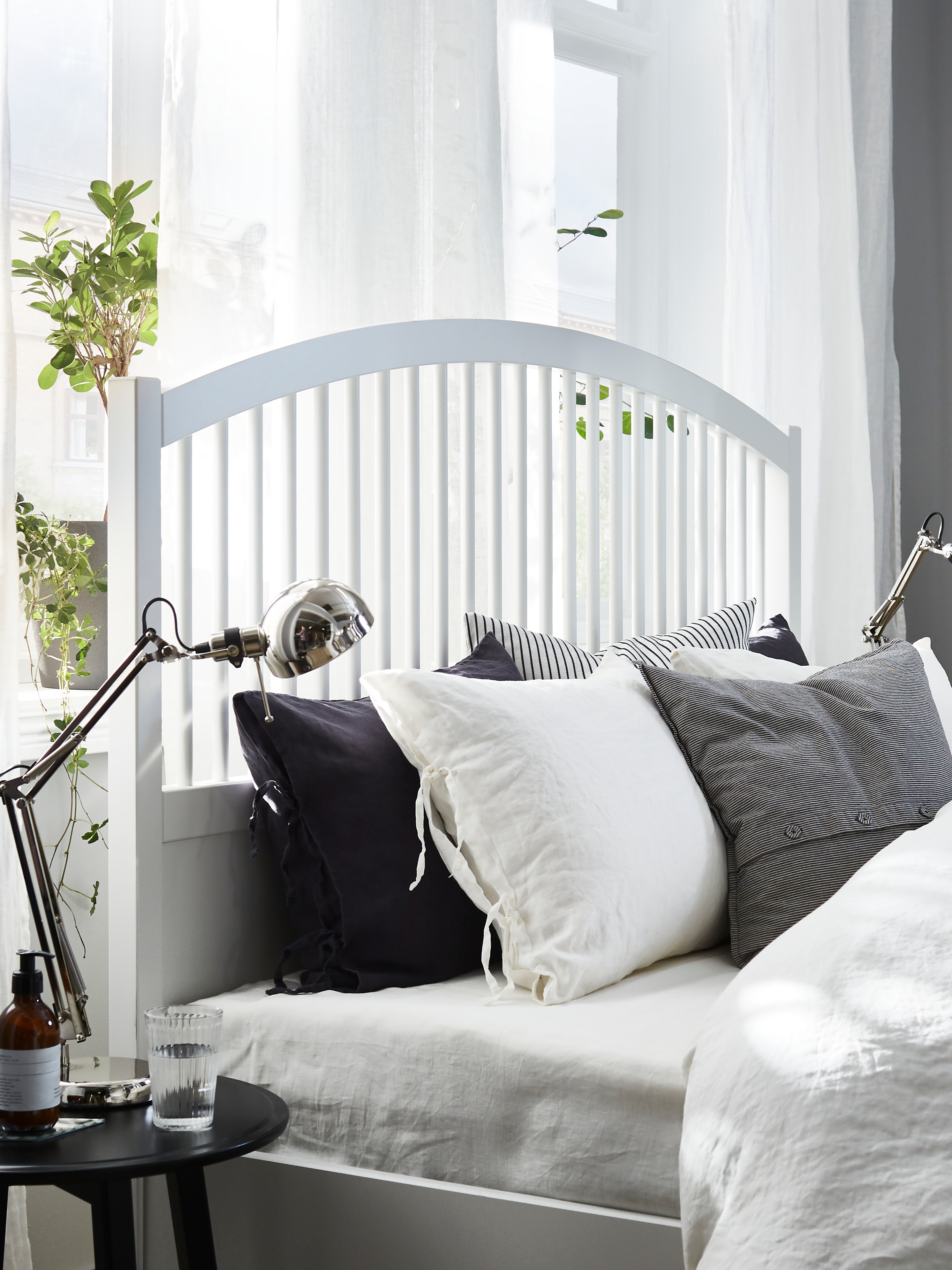 The solid birch, high headboard of a TYSSEDAL bed frame in white with airy spindles behind lots of white and grey pillows.