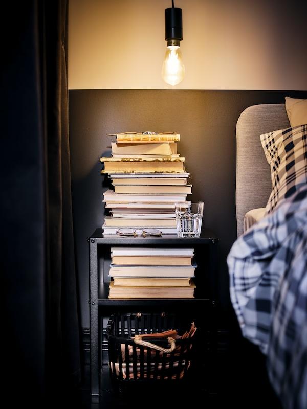 Eine Glühlampe ohne Schirm erhellt ein Bett und einen schwarzen KNARREVIK Ablagetisch, auf dem hohe Buchstapel zu sehen sind.