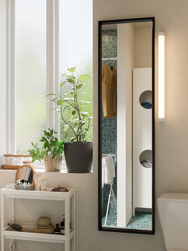 A black full-length mirror, a narrow white cart with toiletries, two potted plants on a windowsill.