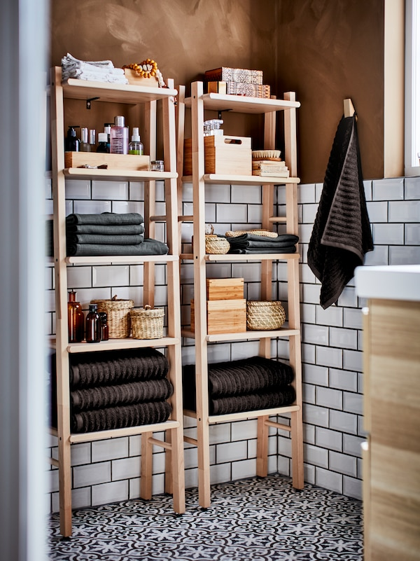A bathroom with white-tiled walls, mosaic floors and brown walls and two VILTO shelving units with towels and accessories.