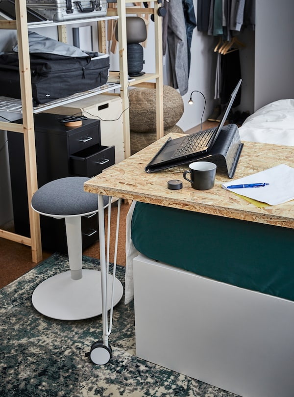 A desk with a black laptop standing on a black BRÄDA laptop support. A cup is next to it, and a white stool is in front.