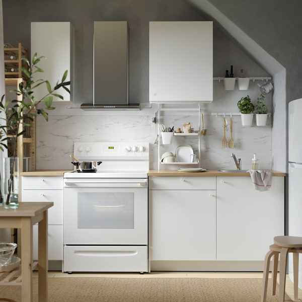 A white KNOXHULT kitchen with a wooden countertop, a rug on the floor and a white oven below a steel extractor hood.