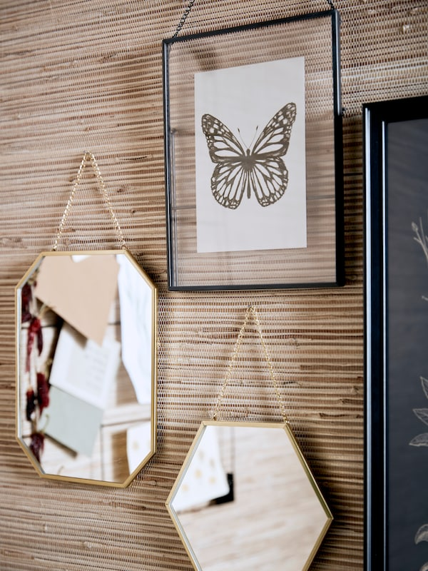 A wall arrangment with mirrors and picure frames.