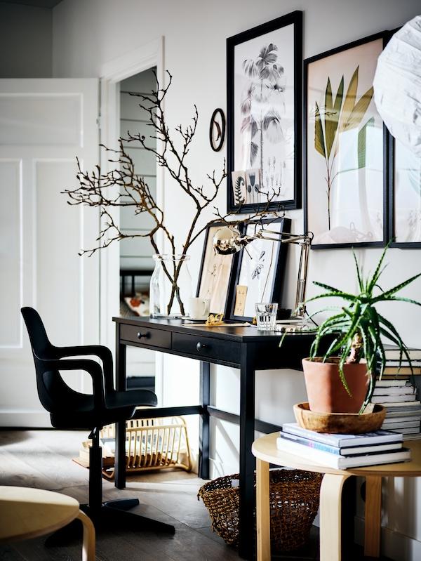 Un bureau HEMNES sur lequel se trouve un vase contenant des branches, contre un mur blanc orné de cadres. Une chaise pivotante est installée devant.