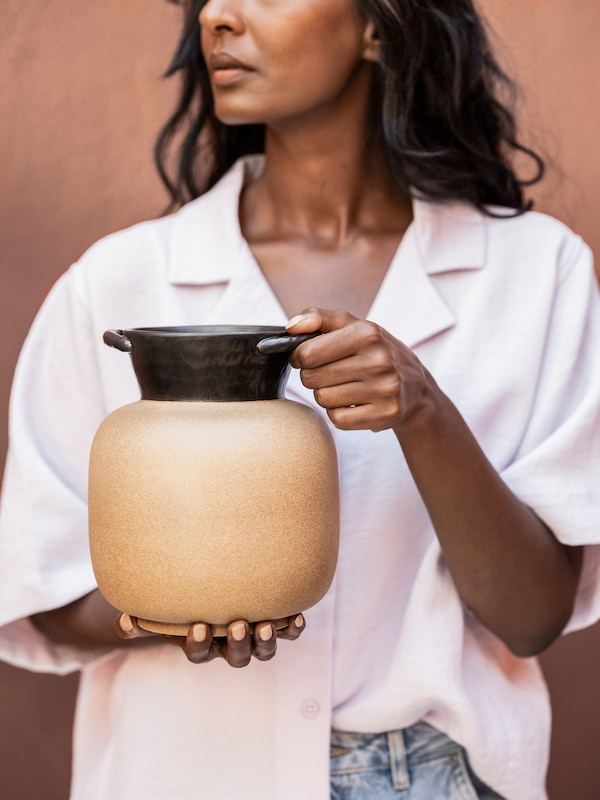 A woman holding a LOKALT ceramic vase with two handles, handmade by skilled artisans in northern Thailand.