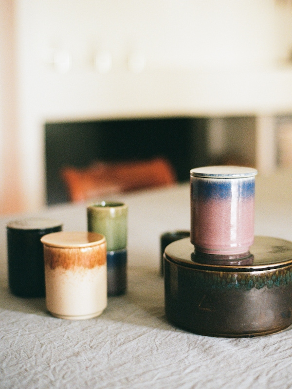 A variety of small and large candles from the OSYNLIG collection in a variety of colors stand on a pale tablecloth.