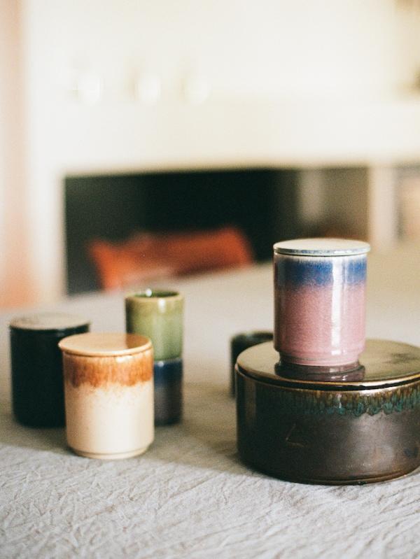 Verschiedene große und kleine Duftkerzen aus der OSYNLIG Kollektion in unterschiedlichen Farben stehen auf einer hellen Tischdecke.