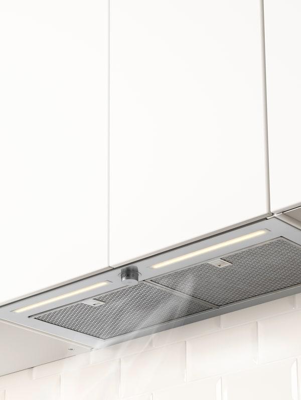 Detalle de un extractor integrado colocado debajo de un armario blanco que succiona el vapor que hay sobre la encimera.