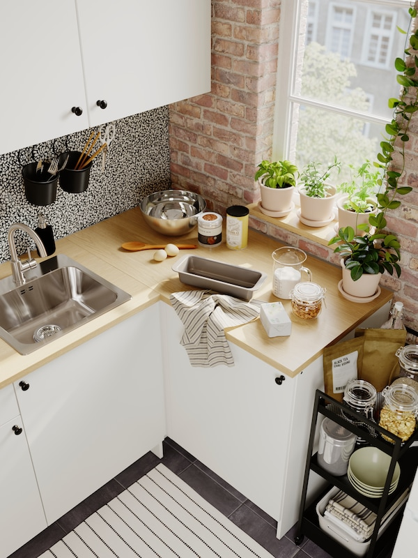 A baking station with an oven tin, kitchen towel, eggs, utensils and ingredients on a kitchen worktop next to a window.