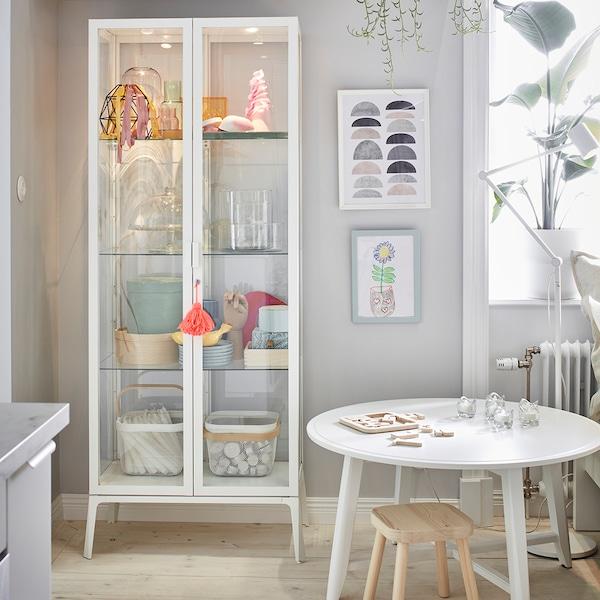 Una sala convertida en home office, donde el escritorio es de la familia LINNMON de IKEA, al lado de un estante KALLAX lleno de artículos personales. Hay también un par de pisos de madera KYRRE y una silla de oficina LOBERGET.
