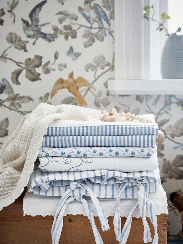 Cortinas y ropa de cama GULSPARV dobladas y apiladas encima de una caja delante de una pared decorada con papel con un estampado forestal.